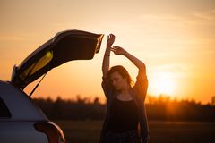 Beautiful young woman happy and dancing in a car`s trunk during a road trip in Europe in the last minutes of Golden Hour stock image