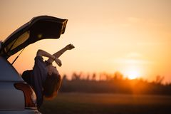 Beautiful young woman happy and dancing in a car`s trunk during a road trip in Europe in the last minutes of Golden Hour royalty free stock photography