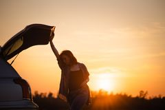 Beautiful young woman happy and dancing in a car`s trunk during a road trip in Europe in the last minutes of Golden Hour stock photography