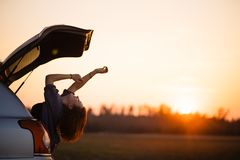 Beautiful young woman happy and dancing in a car`s trunk during a road trip in Europe in the last minutes of Golden Hour stock photos