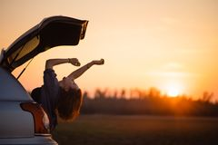Beautiful young woman happy and dancing in a car`s trunk during a road trip in Europe in the last minutes of Golden Hour stock photo
