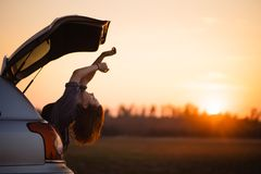 Beautiful young woman happy and dancing in a car`s trunk during a road trip in Europe in the last minutes of Golden Hour royalty free stock image