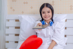 Beautiful young woman happy with headphones and tablets watching movies on the tablet in bed. royalty free stock image