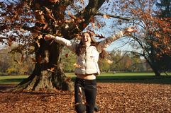 Beautiful young woman happy when leaves are falling in autumn, Monza Park, Milan, Italy Royalty Free Stock Photos