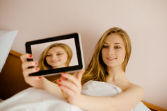 Beautiful young woman happy smiling in bed and Royalty Free Stock Photography