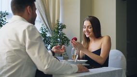 Beautiful young woman is happy and surprised after getting marriage proposal from her boyfriend in restaurant. She is. Saying yes, taking engagement ring and stock video footage