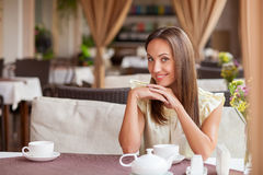 Beautiful young woman has a date in restaurant. Attractive girl is waiting for her boyfriend in cafe. She is drinking tea and smiling. The lady is sitting at the Royalty Free Stock Images