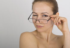 Beautiful young woman has many different emotions, she winks. woman is wearing only glasses Stock Photo