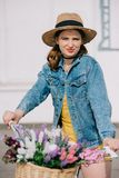 Beautiful young woman in hat and denim jacket riding bicycle and looking. At camera royalty free stock photography