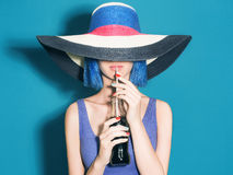 Beautiful young Woman in Hat drink soda. Fashion portait. Elegance Beauty Girl with blue hair. colorful hat stock image