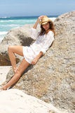 Beautiful young woman with hat leaning against rock on beach Royalty Free Stock Image