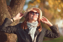 Beautiful young woman in hat and scarf enjoy sunlight Stock Photos