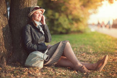 Beautiful young woman in hat and scarf with mobile phone in the Stock Photos