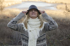 Beautiful young woman with the hat and scarf smiling. In the field, behind lake Stock Photography