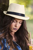 Beautiful young woman with a hat sitting in a park, holding a bo Royalty Free Stock Photo
