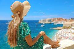 Beautiful young woman with hat sitting on wall looking at stunning panoramic old town of Dubrovnik in Croatia, Europe stock image