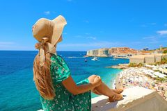 Beautiful young woman with hat sitting on wall looking at stunning panoramic village of Dubrovnik in Croatia, Europe royalty free stock image