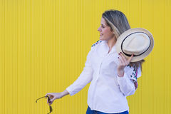 Beautiful young woman with hat and sunglasses having fun. Yellow. Background. Lifestyle. Casual clothing Royalty Free Stock Images