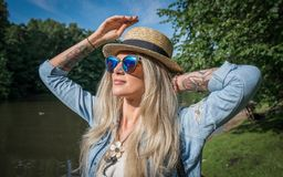 Beautiful young woman in hat and sunglasses resting on the lake in the summer outdoors. The concept of street fashion. Park stock photos