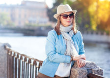 Beautiful young woman in hat, sunglasses and scarf in the city Royalty Free Stock Images