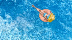 Beautiful young woman in hat in swimming pool aerial top view from above, girl in bikini relaxes and swim on inflatable ring donut. Beautiful young woman in hat royalty free stock image