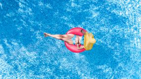 Beautiful young woman in hat in swimming pool aerial top view from above, girl in bikini relaxes and swim on inflatable ring donut. Beautiful young woman in hat stock photos