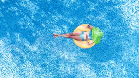 Beautiful young woman in hat in swimming pool aerial top view from above, girl in bikini relaxes and swim on inflatable ring donut. Beautiful young woman in hat stock image