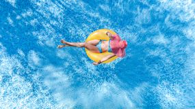 Beautiful young woman in hat in swimming pool aerial top view from above, girl in bikini relaxes and swim on inflatable ring donut. Beautiful young woman in hat royalty free stock photo