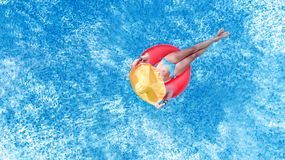 Beautiful young woman in hat in swimming pool aerial top view from above, girl in bikini relaxes and swim on inflatable ring donut. Beautiful young woman in hat stock photo