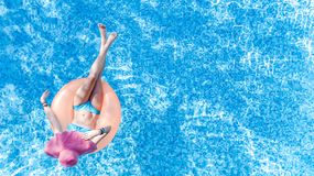 Beautiful young woman in hat in swimming pool aerial top view from above, girl in bikini relaxes and swim on inflatable ring donut. Beautiful young woman in hat stock images
