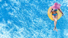 Beautiful young woman in hat in swimming pool aerial top view from above, girl in bikini relaxes and swim on inflatable ring donut. Beautiful young woman in hat royalty free stock photography