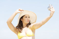 Beautiful young woman in a hat and swimsuit over seaside backgro Stock Photos