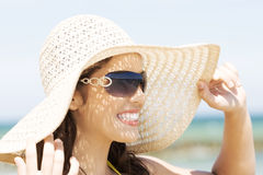 Beautiful young woman in a hat and swimsuit over seaside backgro Stock Image