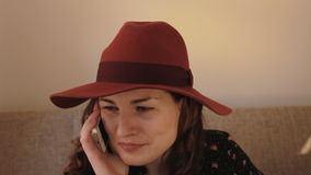 Beautiful young woman in hat talking on mobile phone stock video