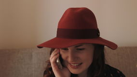 Beautiful young woman in hat talking on mobile phone and smiling stock video
