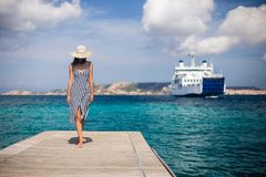 Beautiful young woman in hat walking on wooden pier on Sardinia stock images