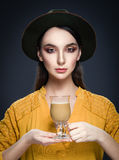 Beautiful young woman in hat and yellow blouse with cup of coffe Stock Photo