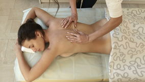 Beautiful young woman having back massage in a spa salon stock footage