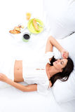 A beautiful young woman having breakfast in bed Royalty Free Stock Photos