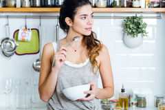 Beautiful young woman having breakfast in the kitchen. Royalty Free Stock Image