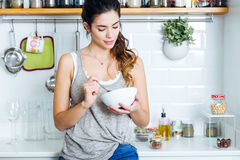 Beautiful young woman having breakfast in the kitchen. Royalty Free Stock Images