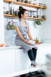 Beautiful young woman having breakfast in the kitchen. Stock Images