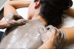 Beautiful young woman having clay body mask apply by beautician. Stock Photo