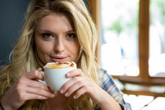 Beautiful young woman having coffee in cafe Royalty Free Stock Images
