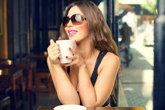 Beautiful young woman having coffee outdoors Stock Photos