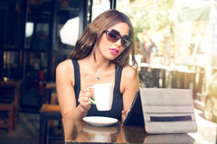 Beautiful young woman having coffee outdoors Stock Photography