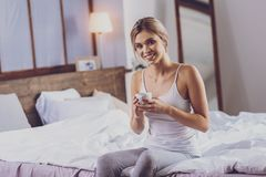 Beautiful young woman having coffee while sitting on bed royalty free stock photography