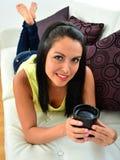Beautiful young woman having coffee sitting on sofa Stock Photo