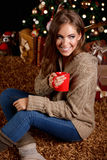 Beautiful young woman having a cup of hot drink Stock Photos