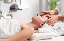 Beautiful young woman having face massage in spa salon royalty free stock images